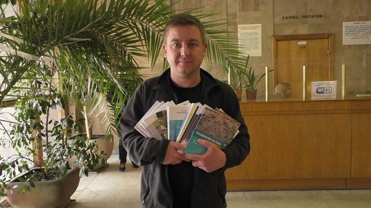 м.н.с.Євген Рибак, пр. сп. відділу комплексного формування бібліотечних фондів, з кількома з подарованих книг