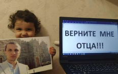 Nadzhiye Mustafayeva (youngest child of Server Mustafayev) with a photo of her father, next to the message Bring my father back Photo Crimean Solidarity